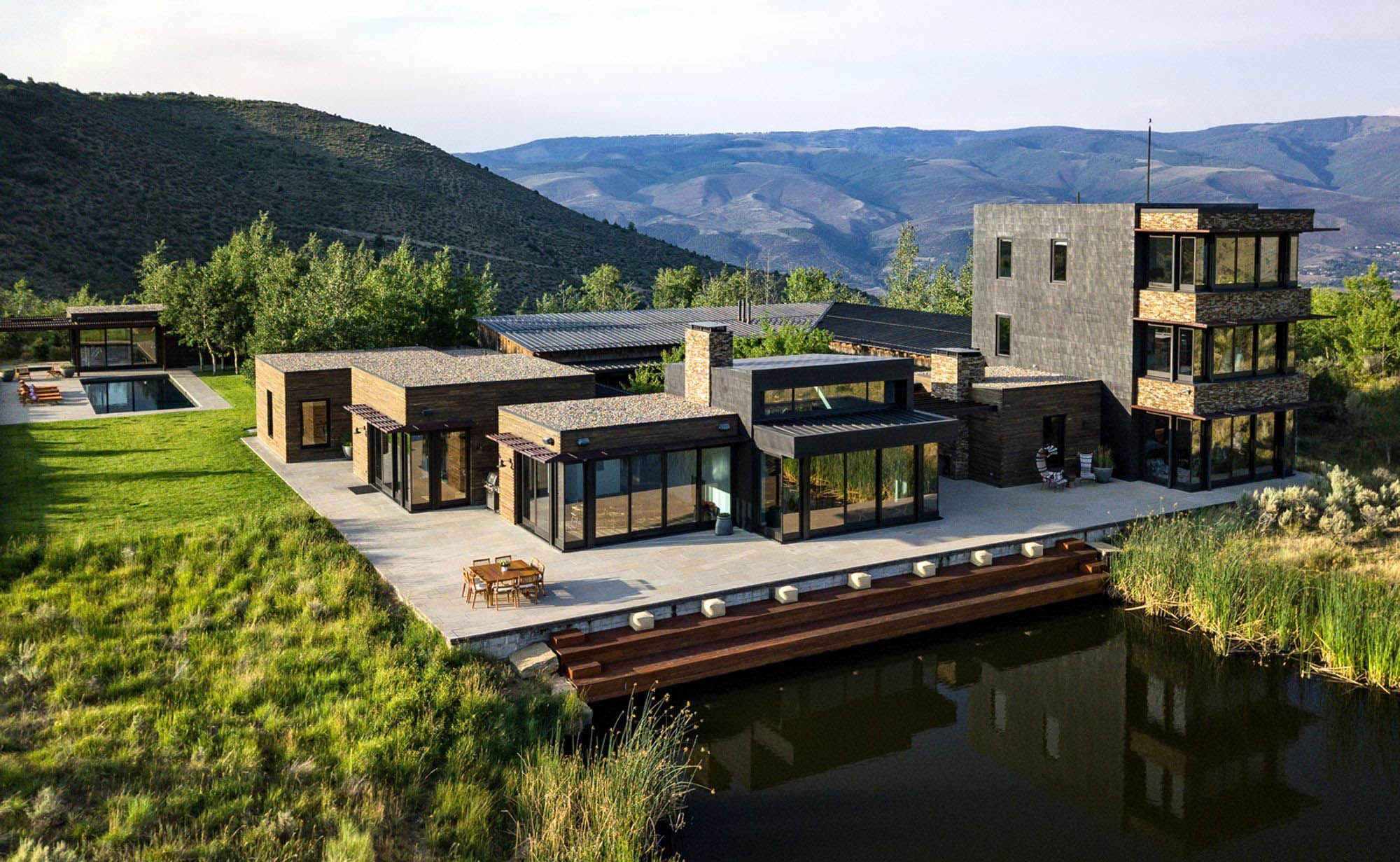 modern black country home with stone veneer siding and metal siding flat roof design