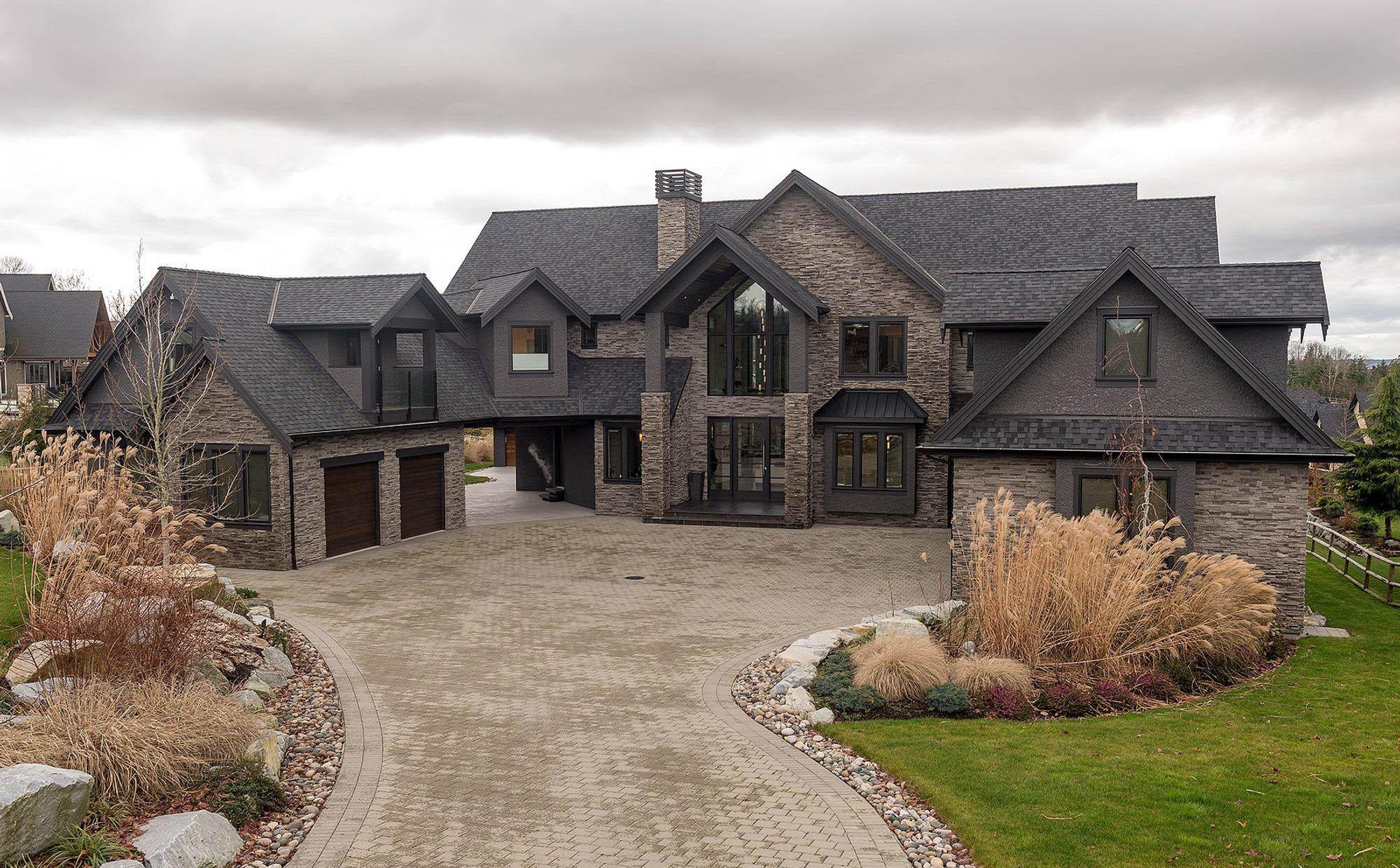 black and gray home with lots of stone veneer black framed windows and doors dark wood garage doors