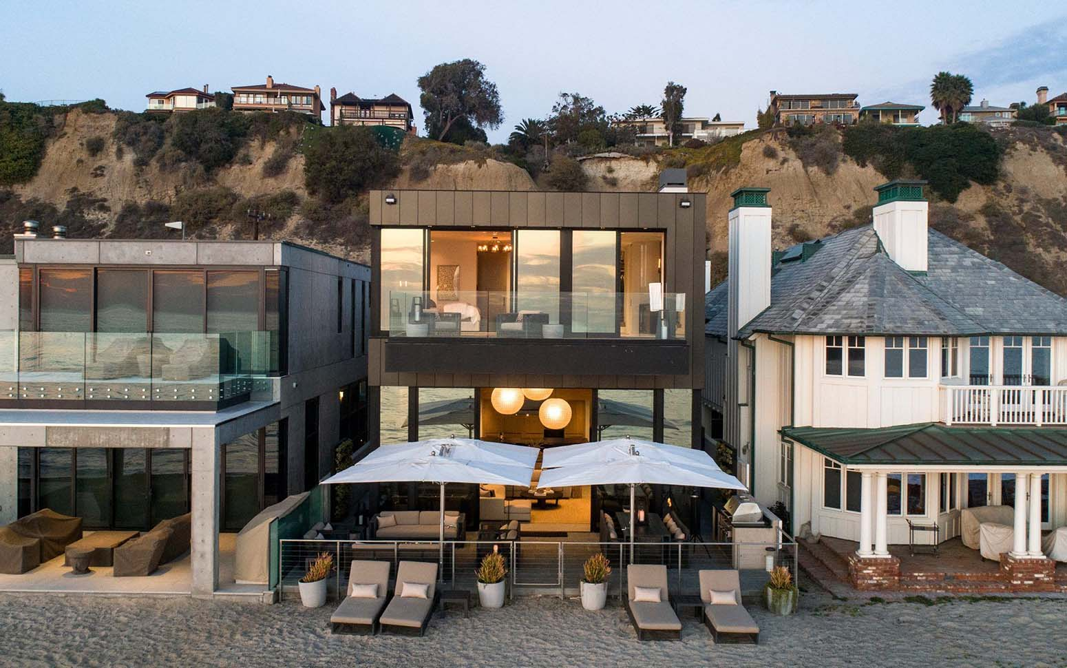 modern black metal siding beach house with big glass windows