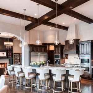 Luxury high end kitchen with dark wood floors, cabinets and coffered ceiling with exposed real wood beams.