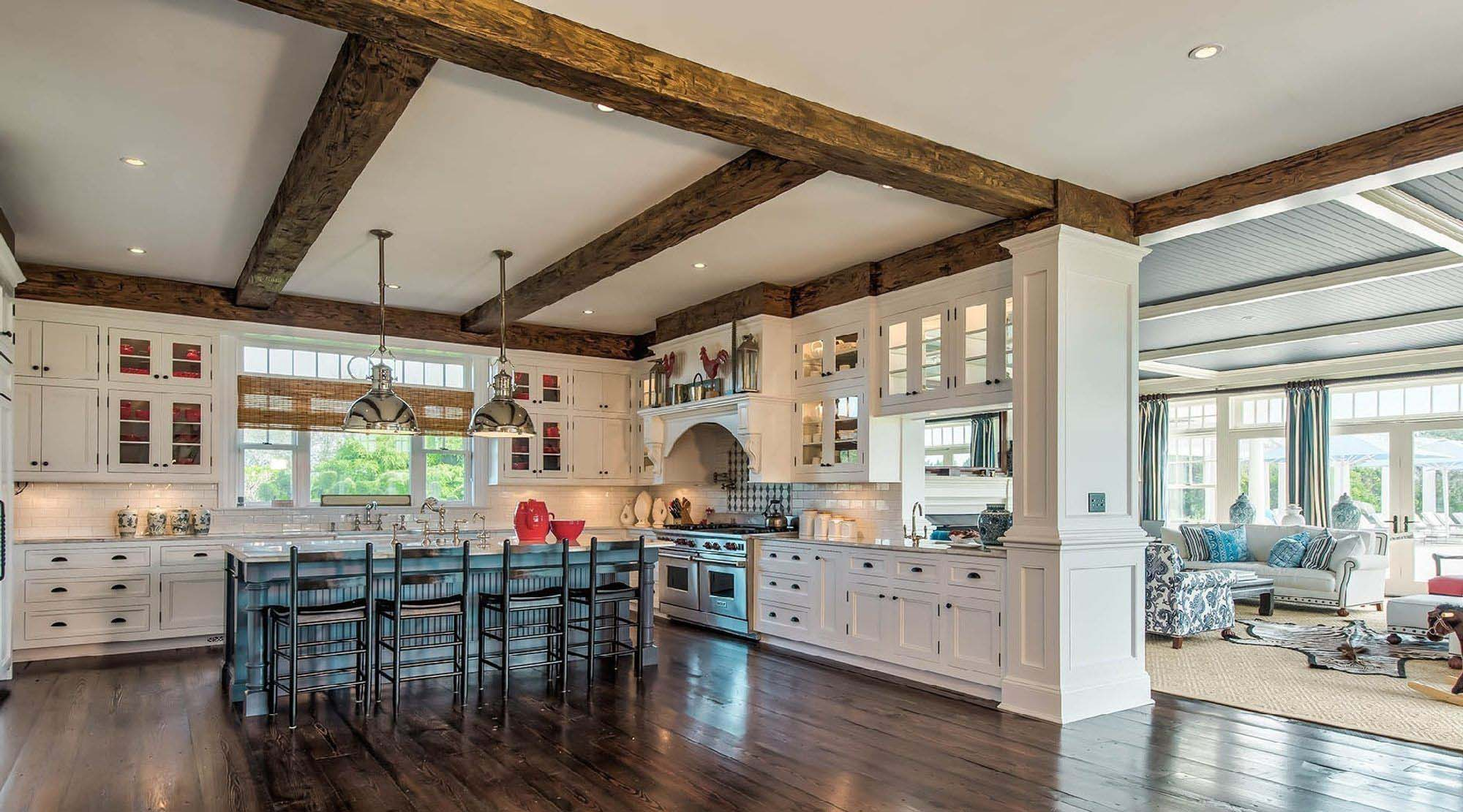 exposed real wood ceiling beam in the kitchen white cabinets open floor plan
