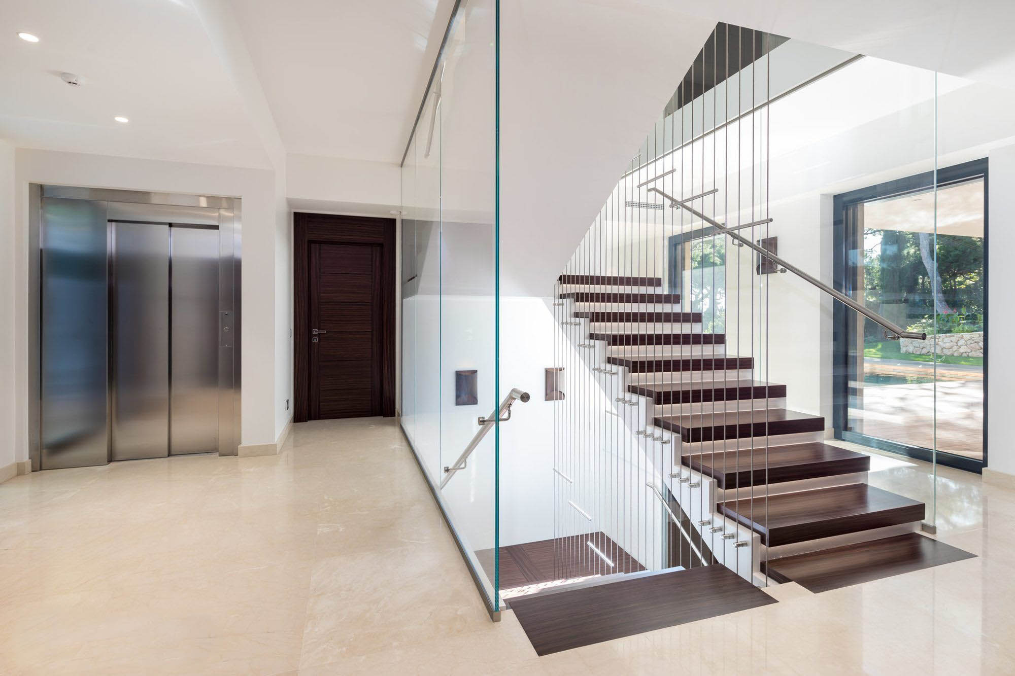 Modern wood, wire and glass wall staircase. Dark wood steps with white risers. Glass and wire sidewalls.