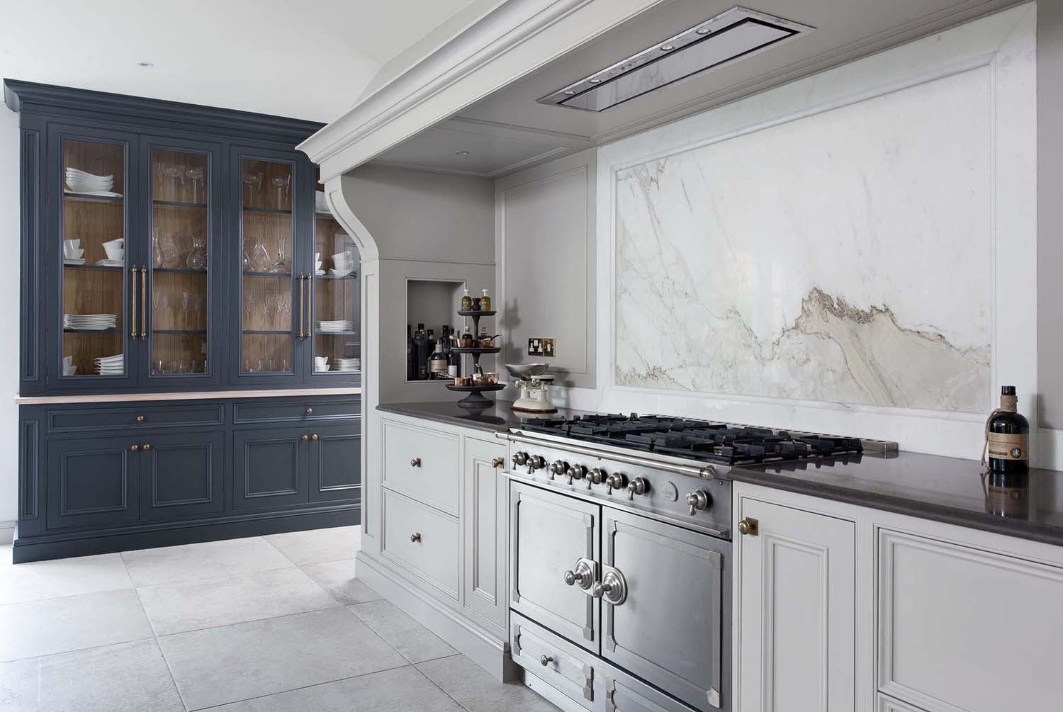 white marble kitchen backsplash with stainless stove and white cabinets
