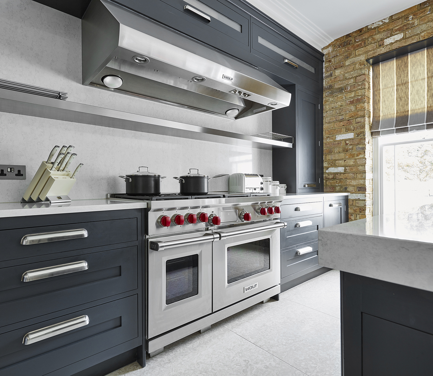 gray quartz backsplash and matching countertops with red brick kitchen accent wall