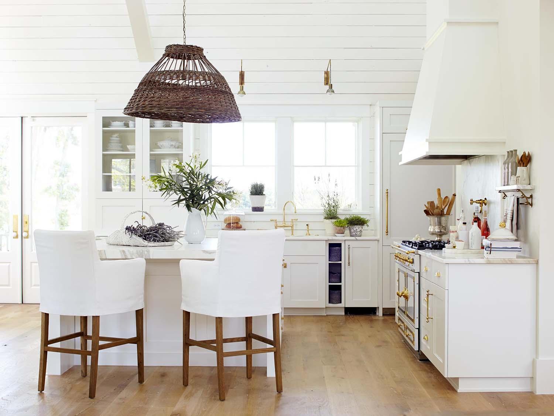 Light and Bright kitchen design white cabinets with gold hardware, marble slab oven backsplash.