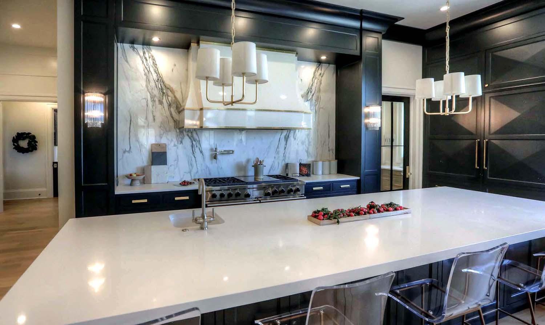 marble slab backsplash with black cabinets white range hood