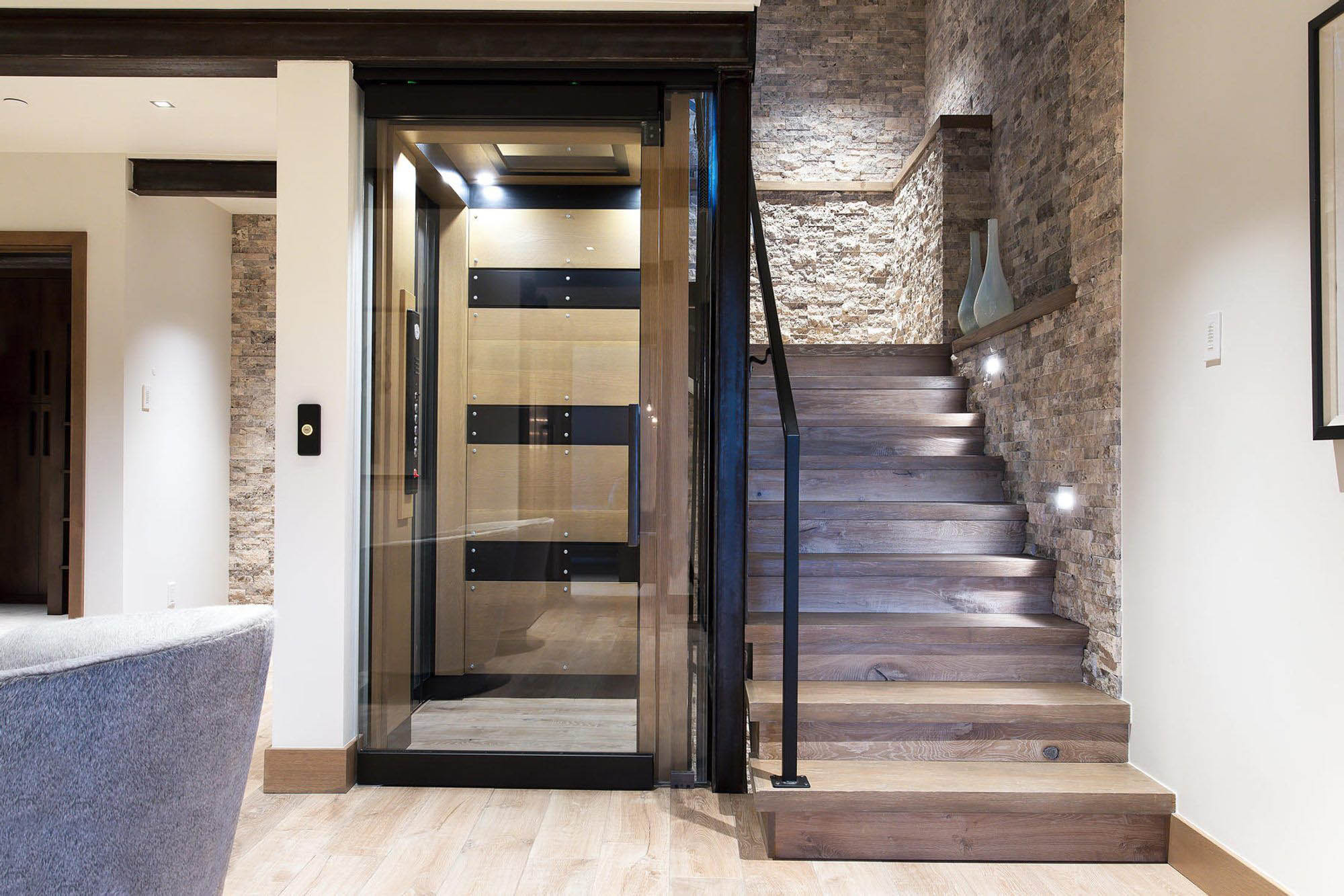 Beautiful modern staircase design with light gray wood and matching stone wall veneer. Black metal railings. Matching hardwood floors.