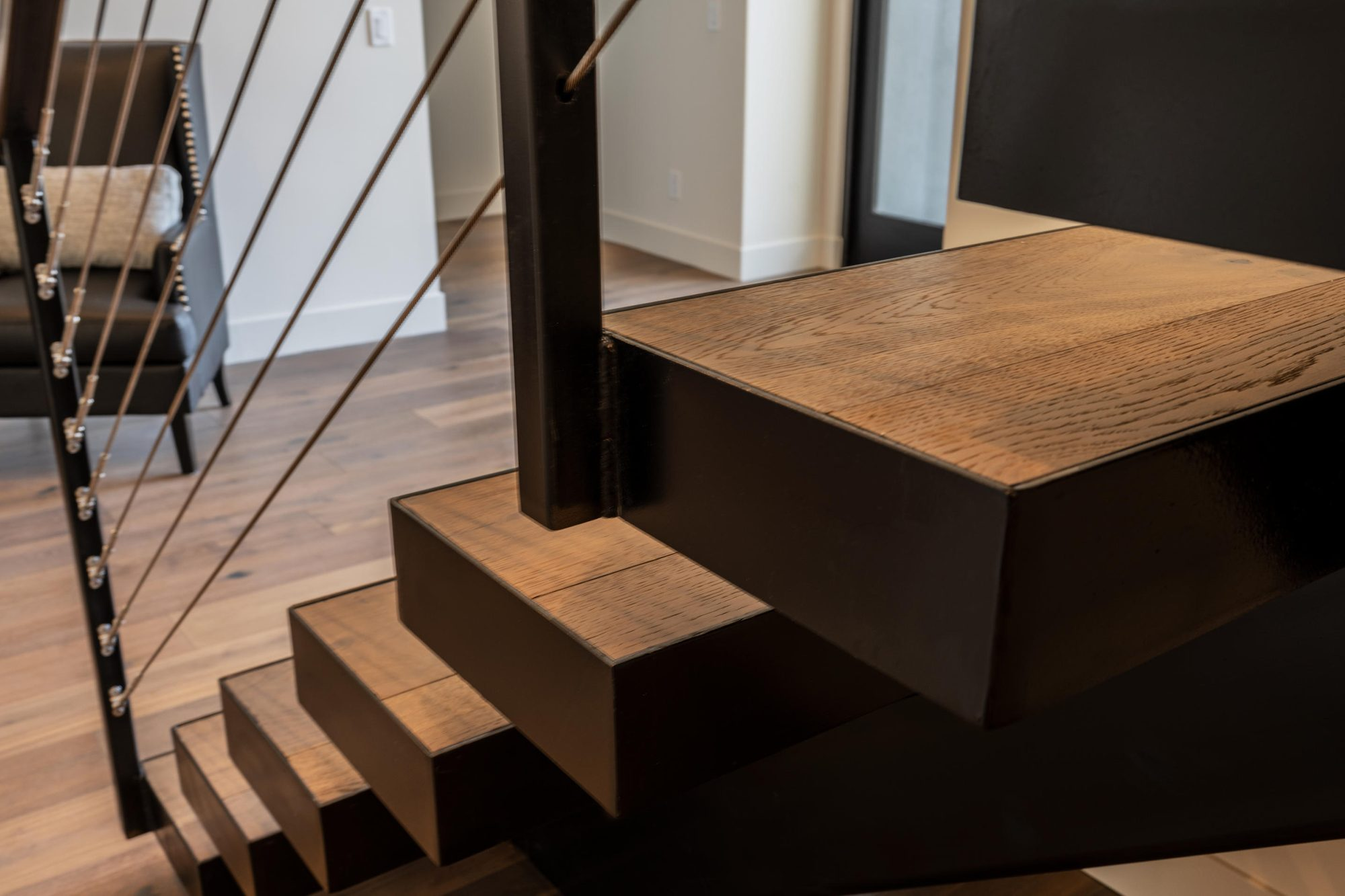 Closeup detail photo of a modern staircase. Open frame staircase with metal backbone and wood steps. Wire railings.