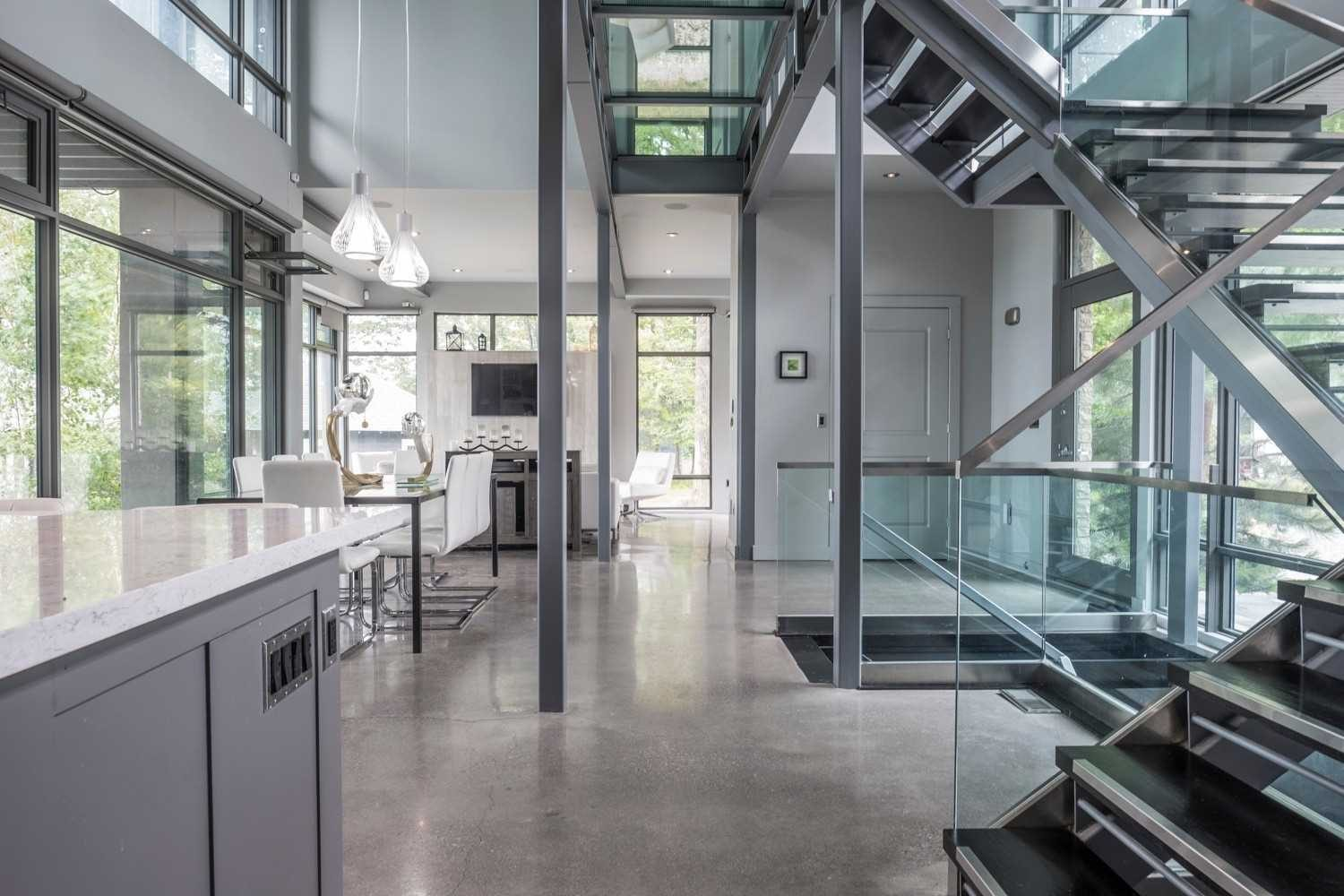 Ultra modern glass and metal staircase design. Concrete floors. Industrial design.
