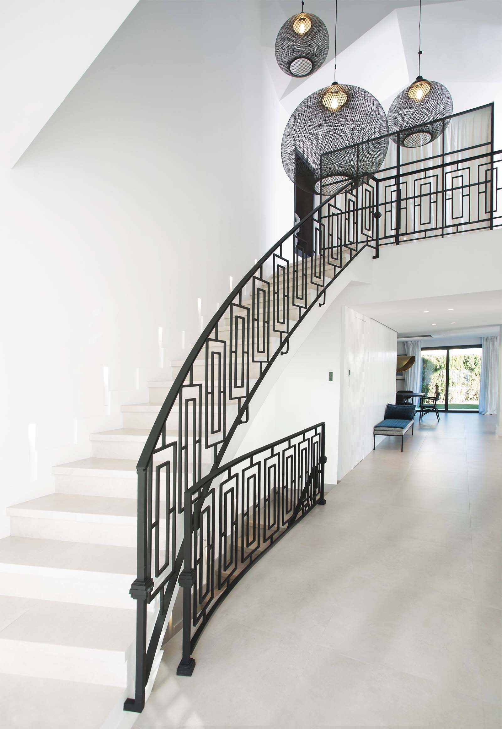 Beautiful modern white staircase with custom made black iron railings. Curved staircase design. Modern transitional style.