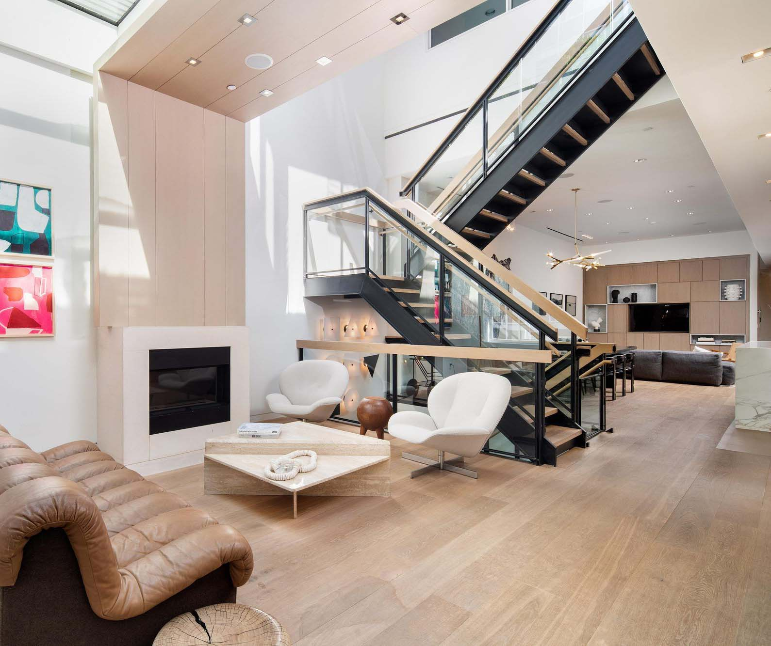 This beautiful staircase appears to float without any supports under the platform. Back steel with wood. Glass railings.