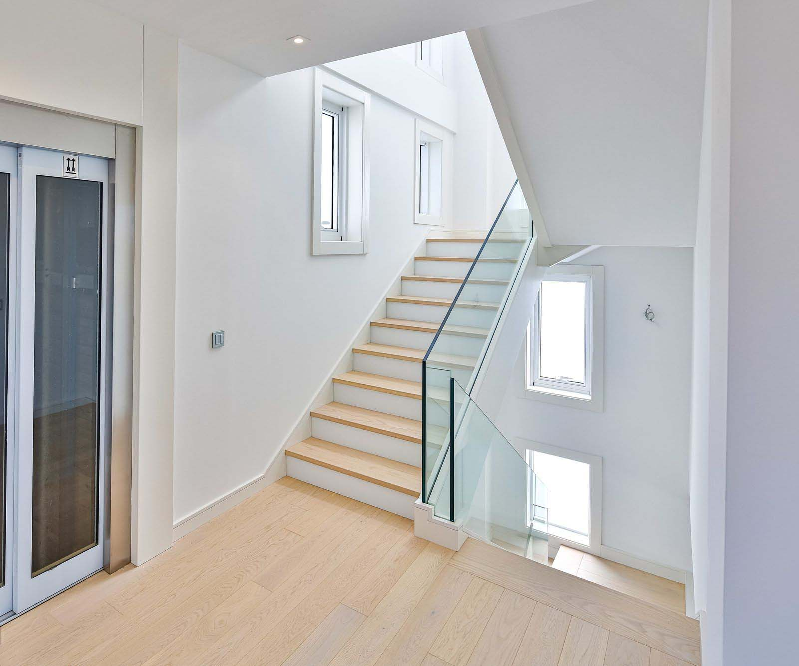 Light and bright modern staircase design. Light hardwood floors and steps with white risers and glass railings.