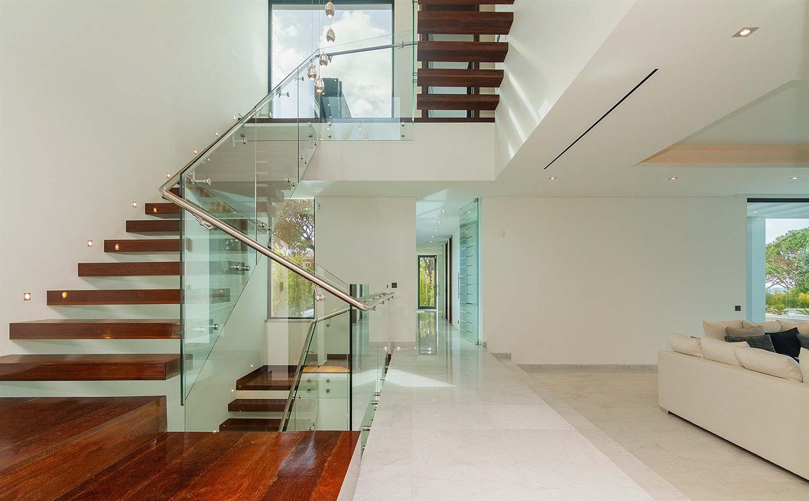Modern floating wood steps with glass railing. These steps appear to come straight through the walls
