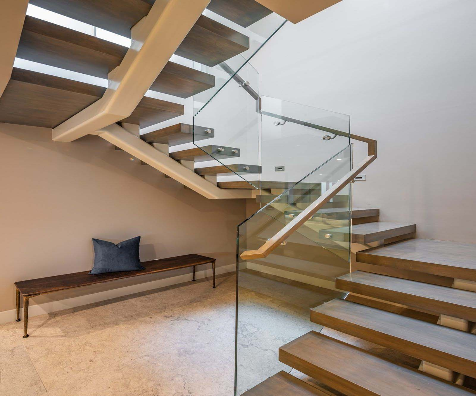Modern staircase with center steel backbone. Wood steps and glass railings with wood handrail.