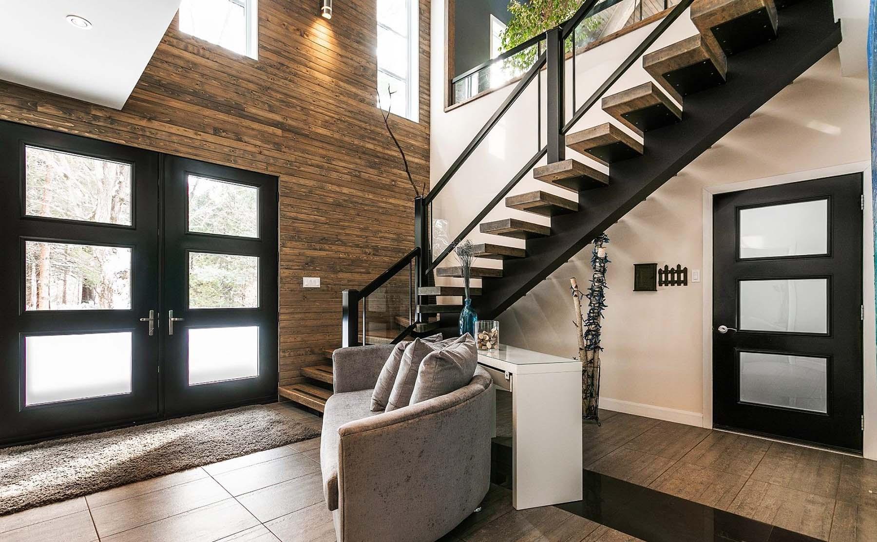 Beautiful modern staircase with black steel backbone frame and floating wood steps. Glass and black metal railings.