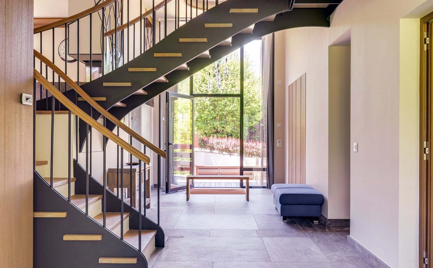 Cool modern staircase with black metal frame and floating wood stairs. Black metal balusters and wood hand rail. Winding staircase style.