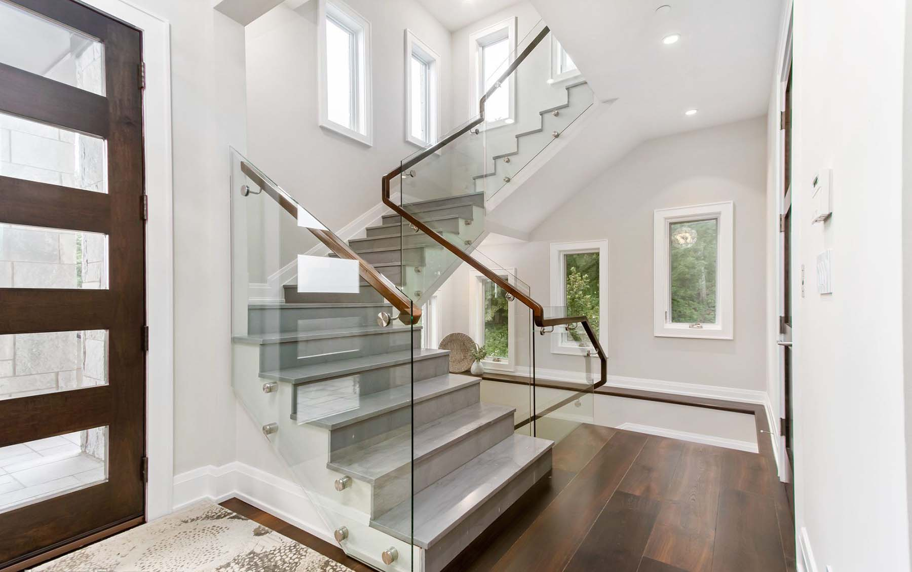 Gray tile steps with matching white risers, glass railings and wood hand rail. Winding floating staircase.