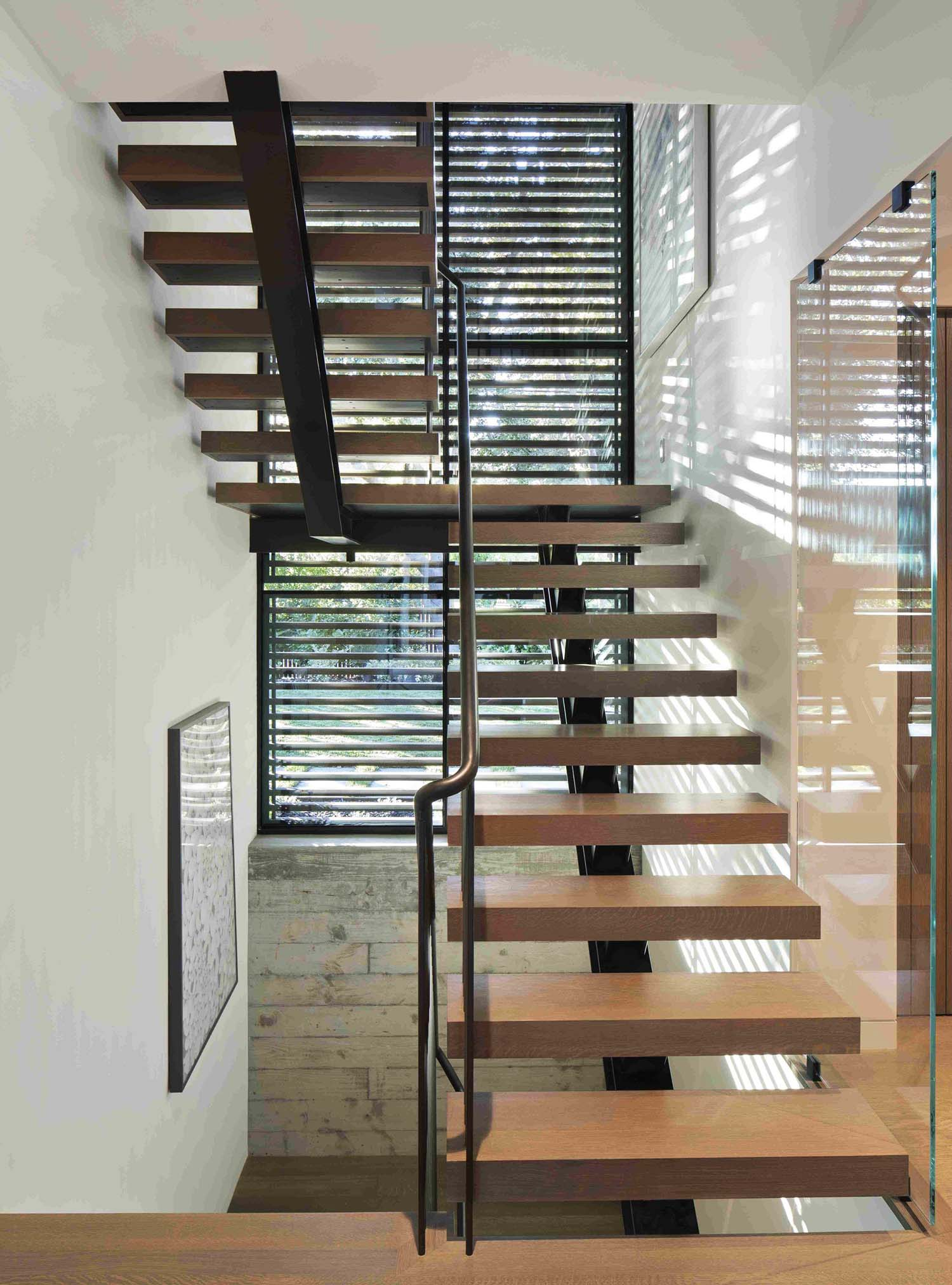 Center black steel backbone support with wood steps. Open risers.