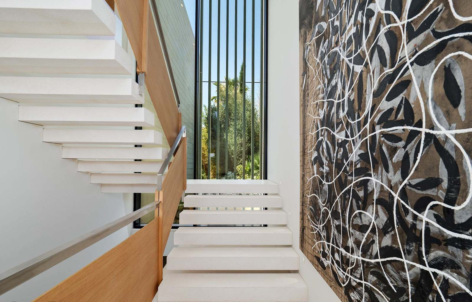 Modern floating staircase with white steps and wood rails. stepsfloating from the side walls.