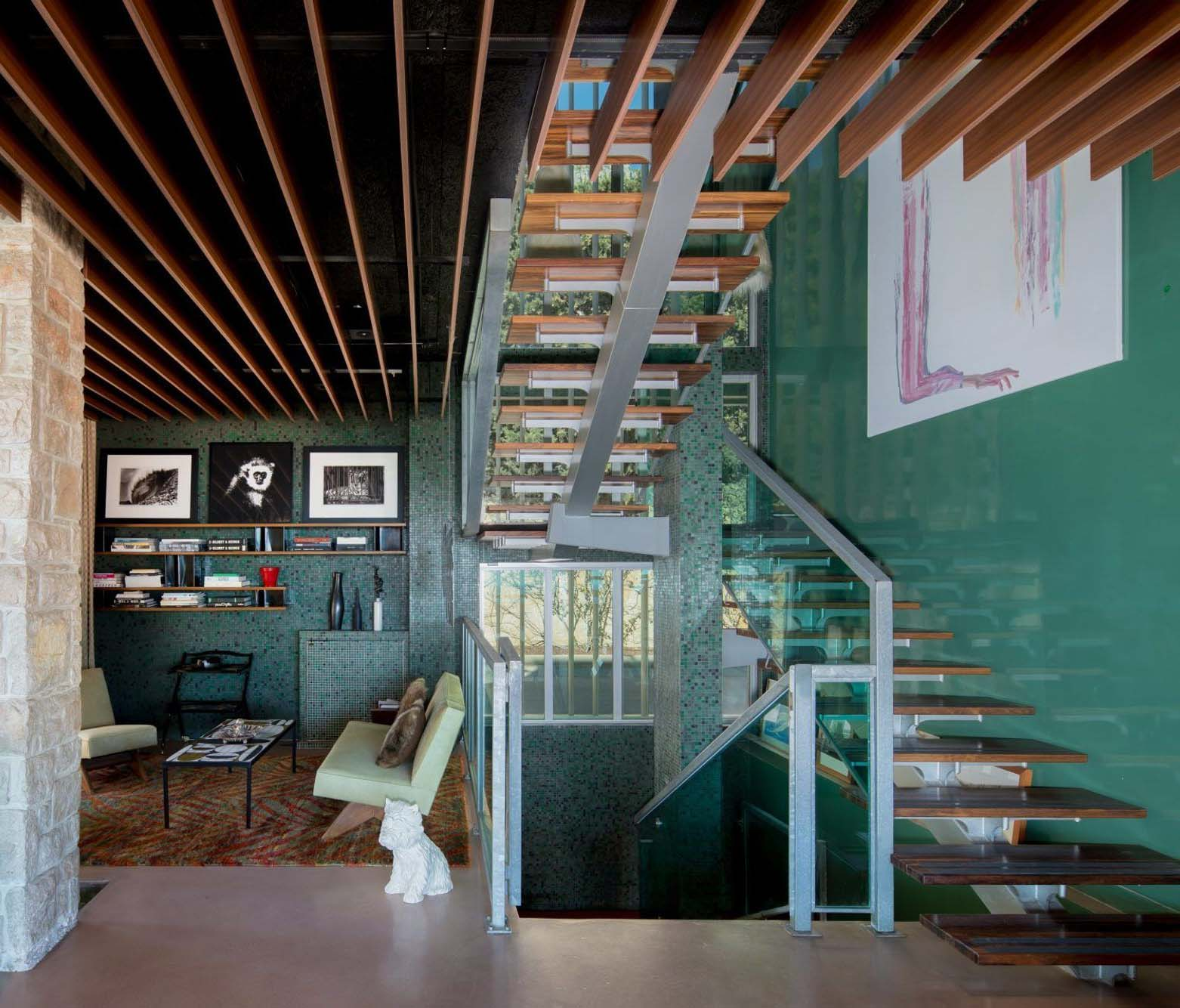 These wooden steps are supported by a single steel frame backbone. Glass railings.