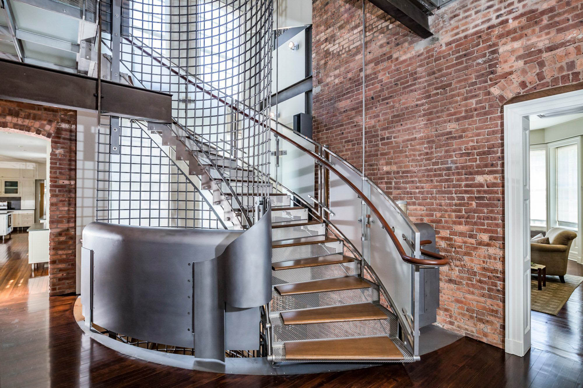 Modern industrial staircase design with aluminum, steel, wood and glass. Red brick walls and dark stained hardwood floors.