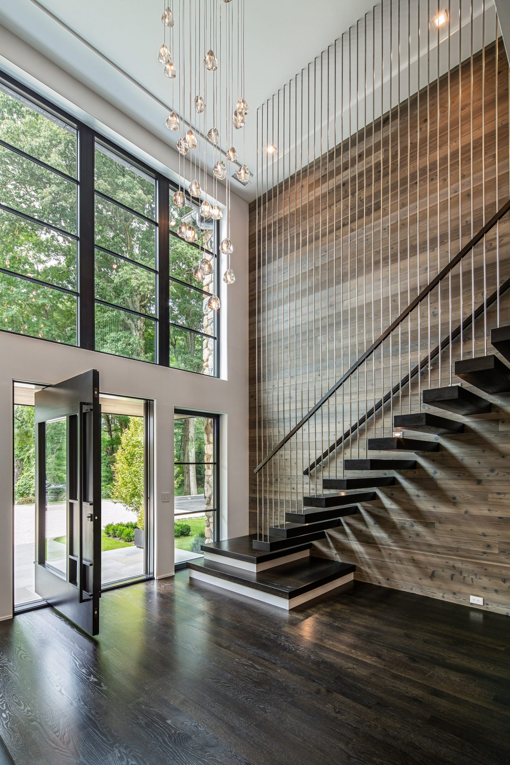 Modern home with a floating staircase built into the wall with tread to ceiling metal balusters.