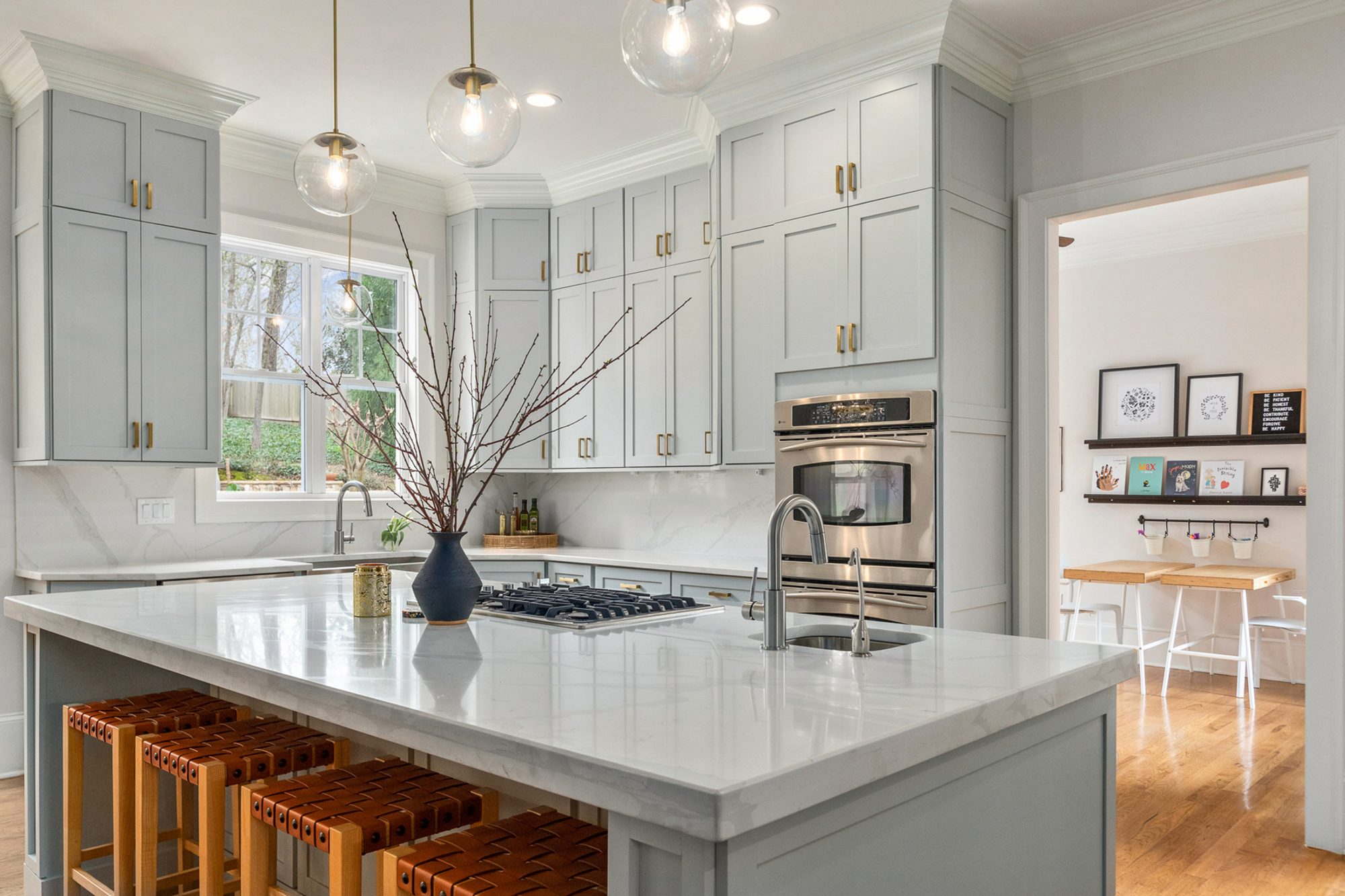 Pale gray shaker style cabinets with solid slab marble quartz backsplash.
