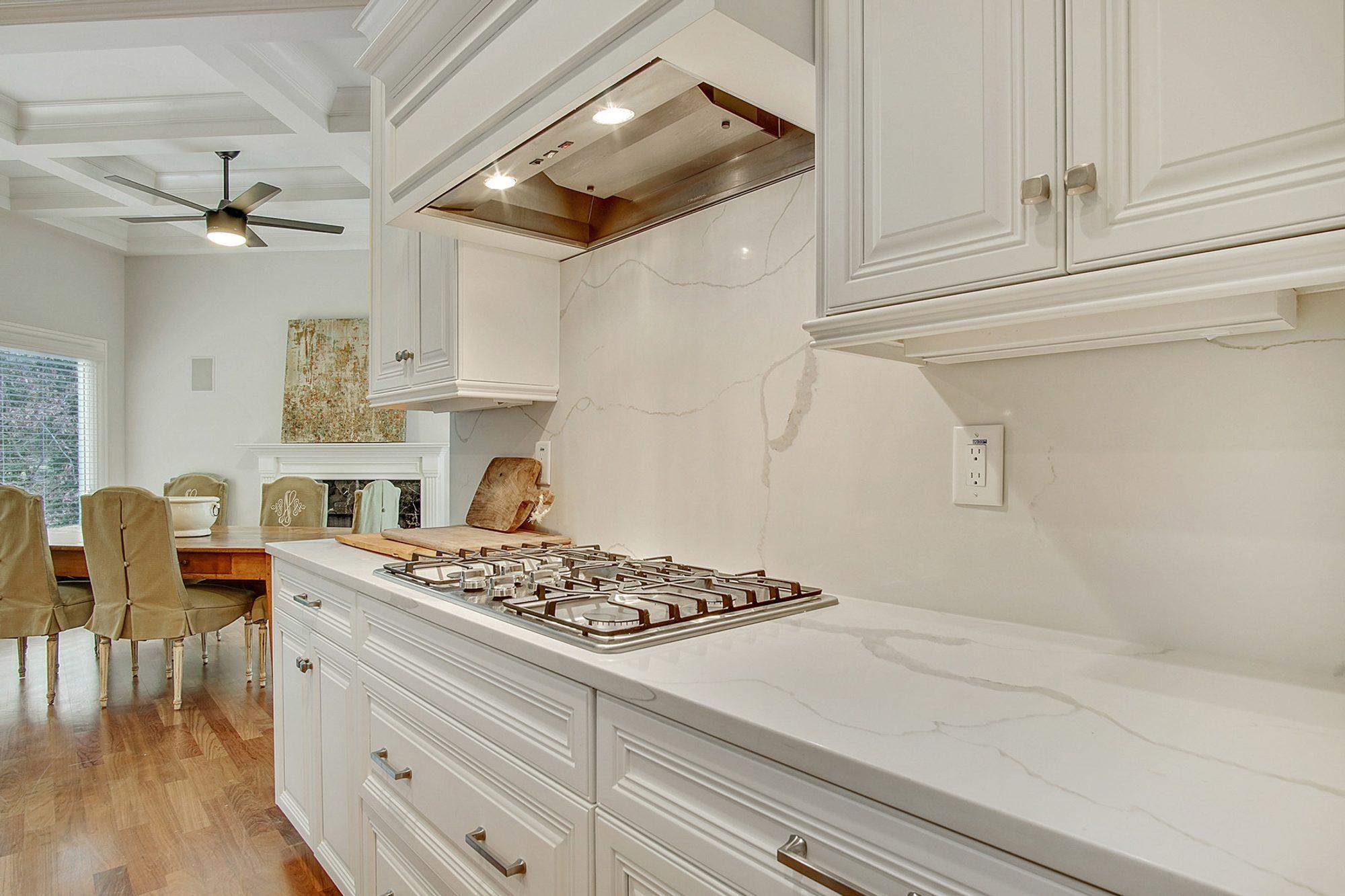 White kitchen cabinets with solid marble quartz backsplash.