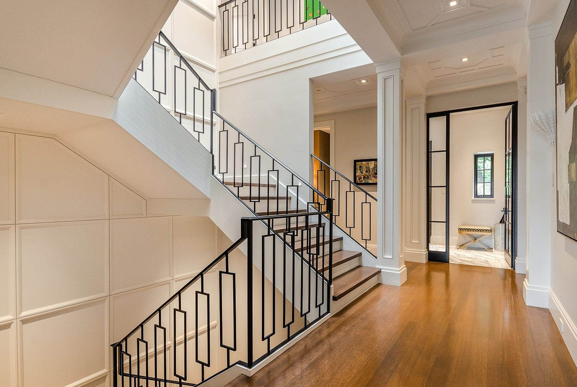 Transitional modern staircase design made with black iron. Custom wall paneling adorns the stair walls. Wood floors with white risers.