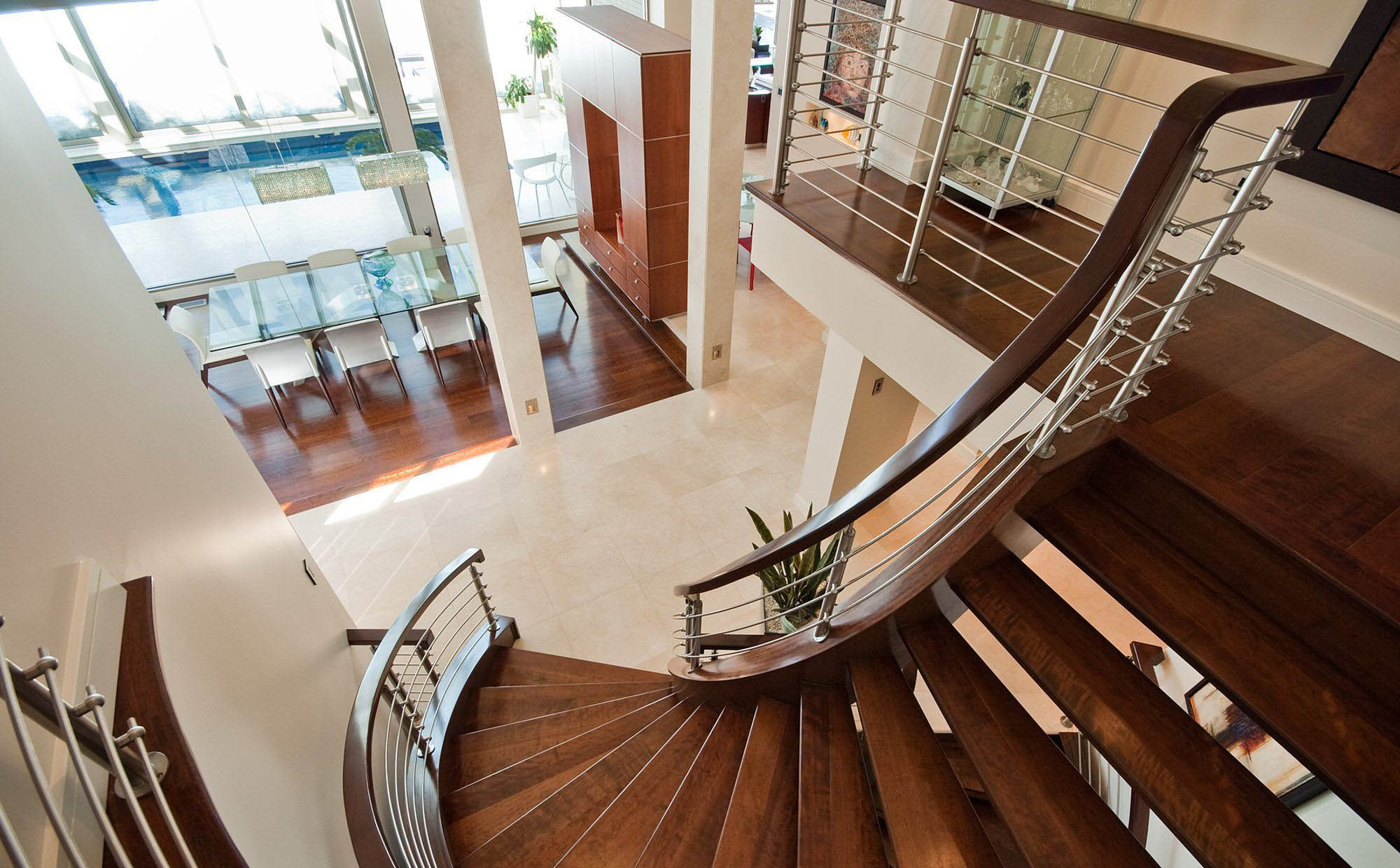 Beautiful curved wood modern staircase design with metal balusters and wood hard rail. Matching hardwood floors. Dark brown stain with a light sheen.