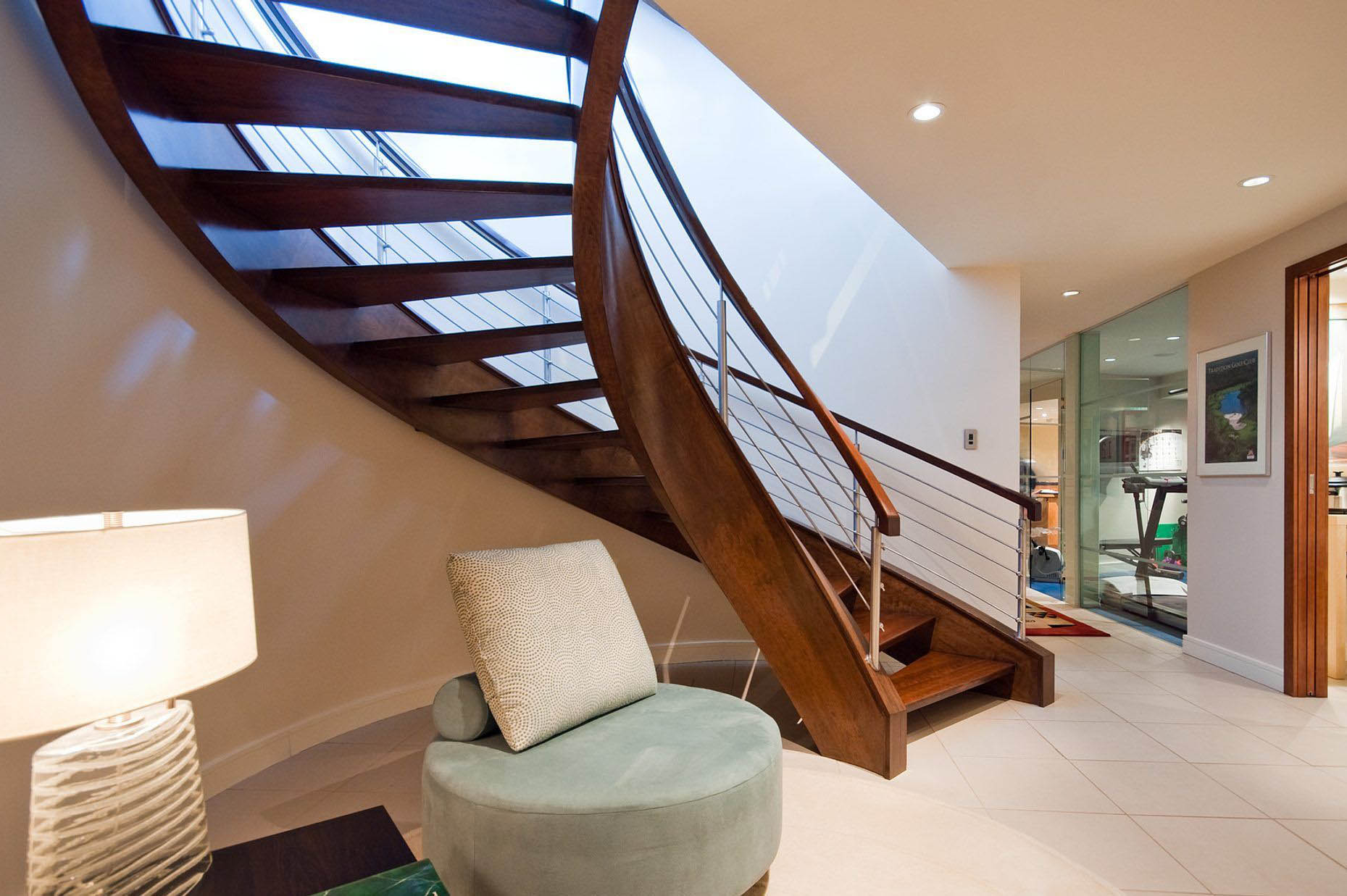 Sexy curved modern staircase design with real wood stained a medium brown. Open risers. metal balusters with wood rail.