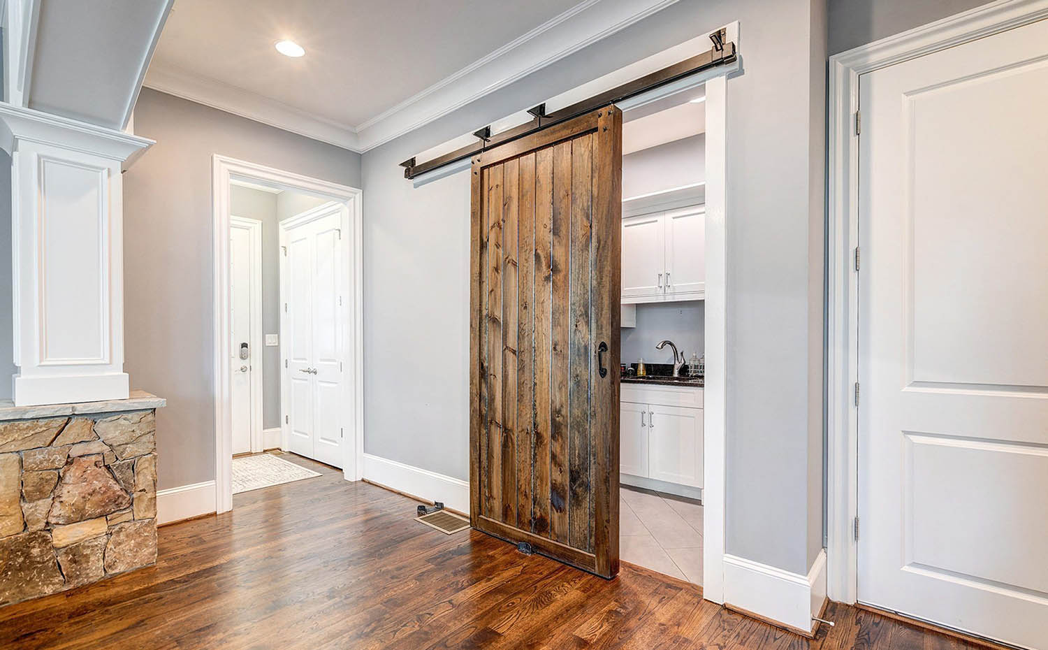Reclaimed wood prep kitchen barn door with black mounting hardware and handle. Matching hardwood floors with gray walls, white trim and real stone interior veneer.