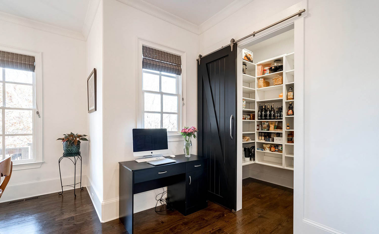 Black sliding pantry door with brushed metal mounting hardware and handle.