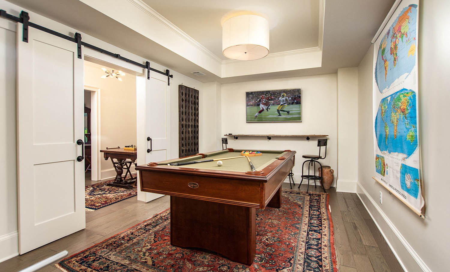 White wooden french barn doors with black handles and hardware. Game room with pool table and medium stained wood floors.