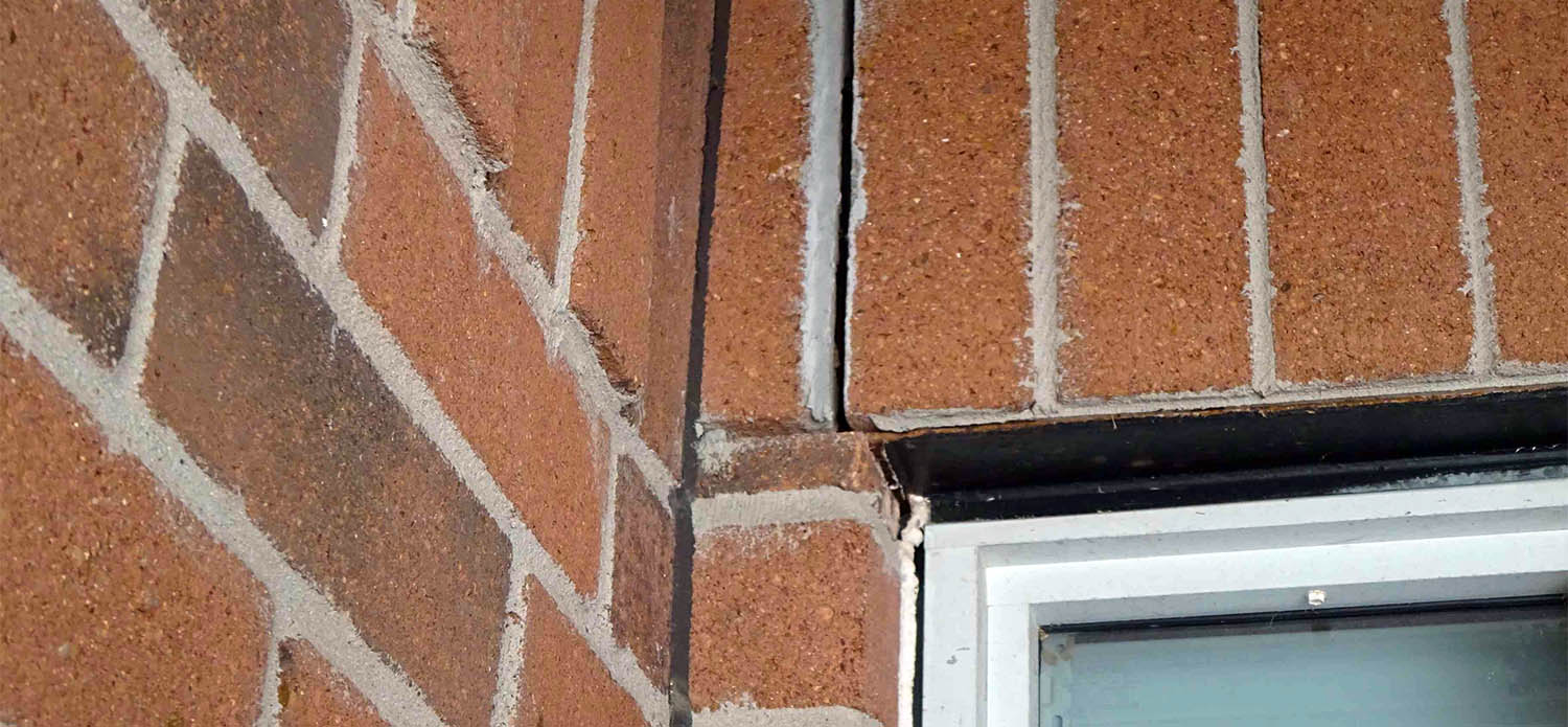 Cracked brick veneer joints due to a failed metal lintel.