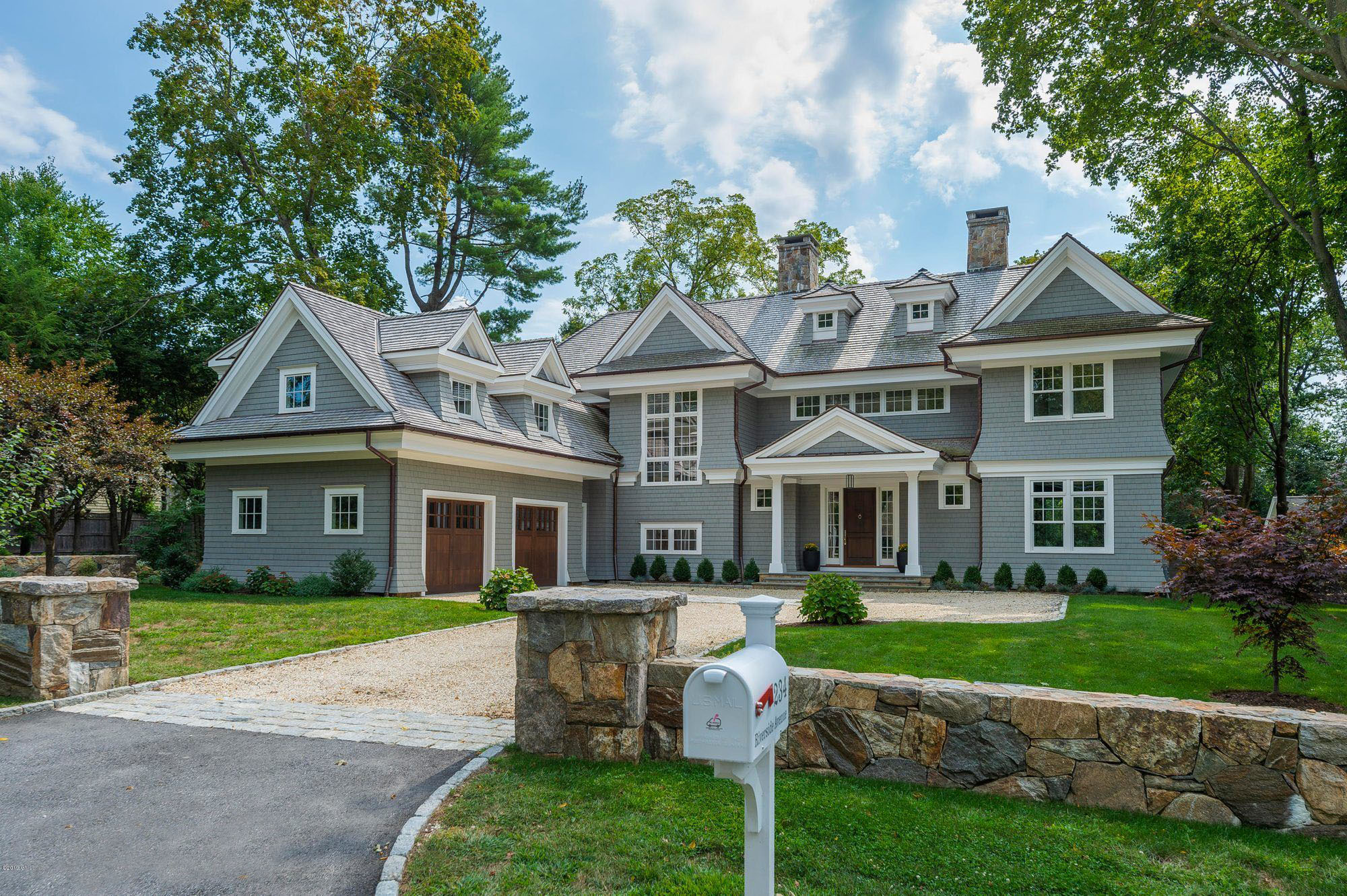 gray house color scheme with white trim and stained wood garage and front door. real stone veneer.