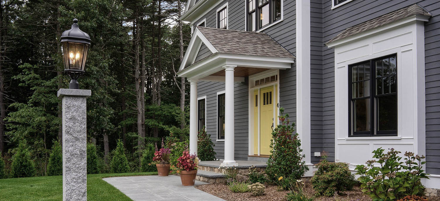gray home with yellow front door and white trim black framed windows