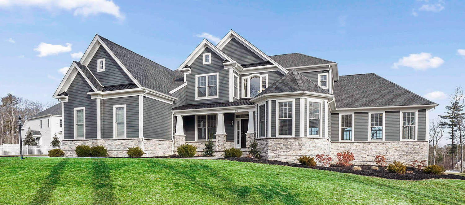 gray house with real stone veneer and black front door and white trim