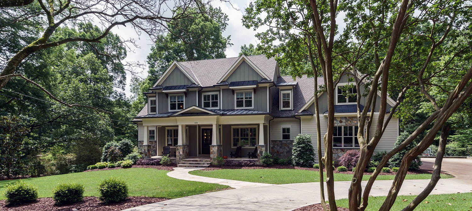 gray home with real stone and vertical siding gray and white siding black metal roof