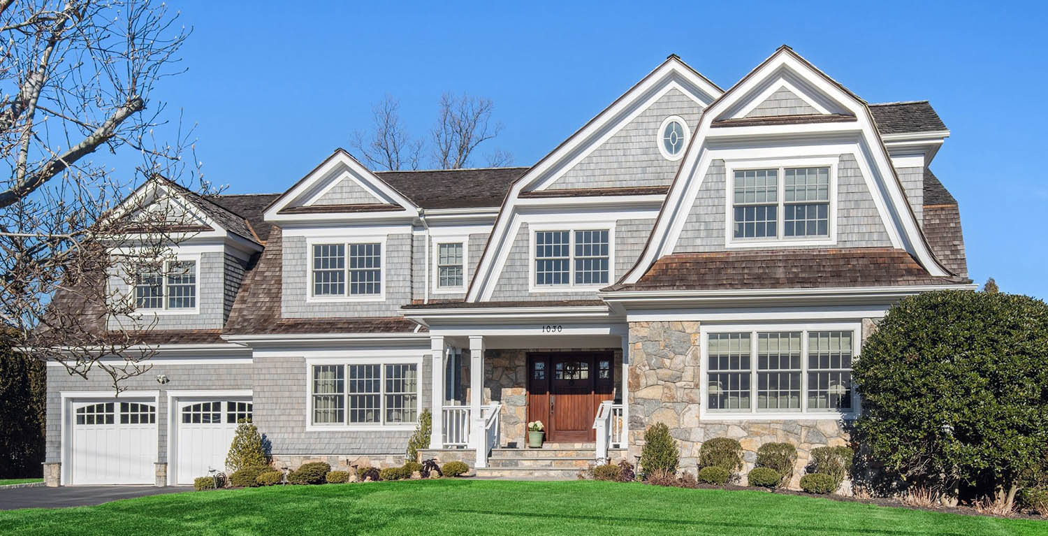 gray house cedar shake siding with real stone veneer white trim brown roof