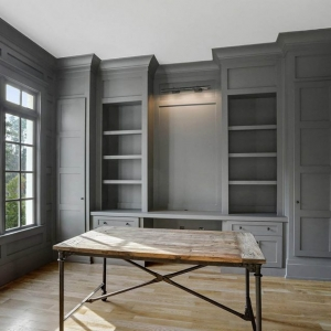Wood walls painted gray with wall penling and built ins. Square shaker style trim design.