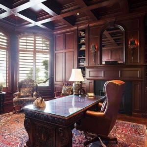 Home office with mahogany wood walls and matching coffered ceiling.