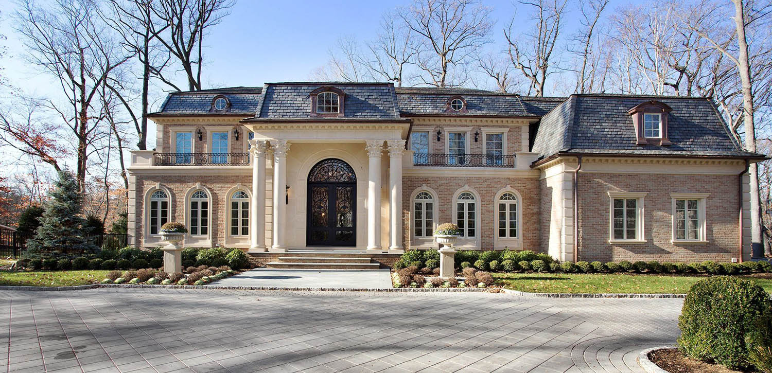 Beautiful light brick custom home with concrete cast trim and accent. Huge front double columns. Black front door with arched transom.