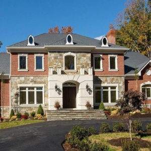 Red brickhome with stone and stucco veneer. Dormers on a black shingled roof. Stone steps.