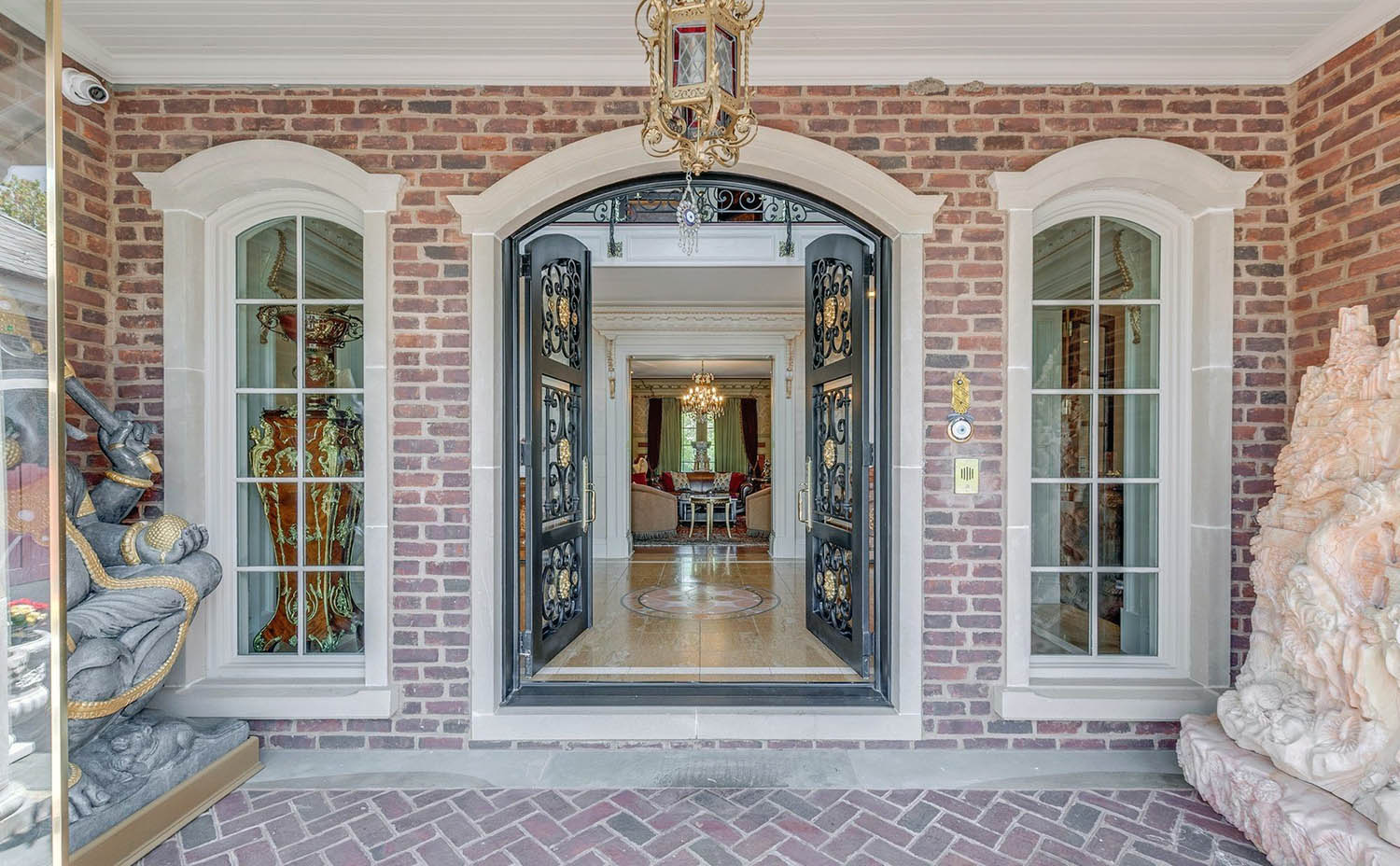 Black arched front door with glass and custom scroll work. Red brick with concrete formed trim.