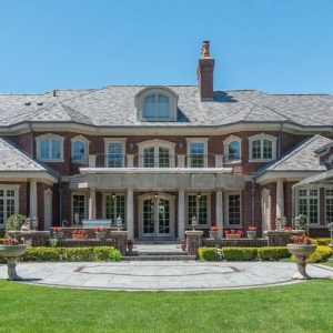 Huge red brick veneer estate house with tan stone trim and columns. Gray roof shingles. Red brick retaining walls. Arched dormer.