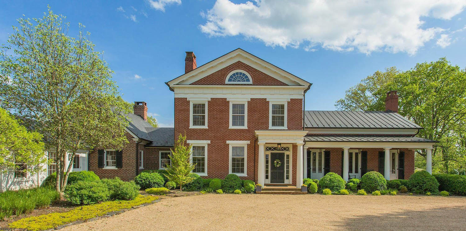 redbrick custom home with a combination asphalt and black metal roof with white columns and trim
