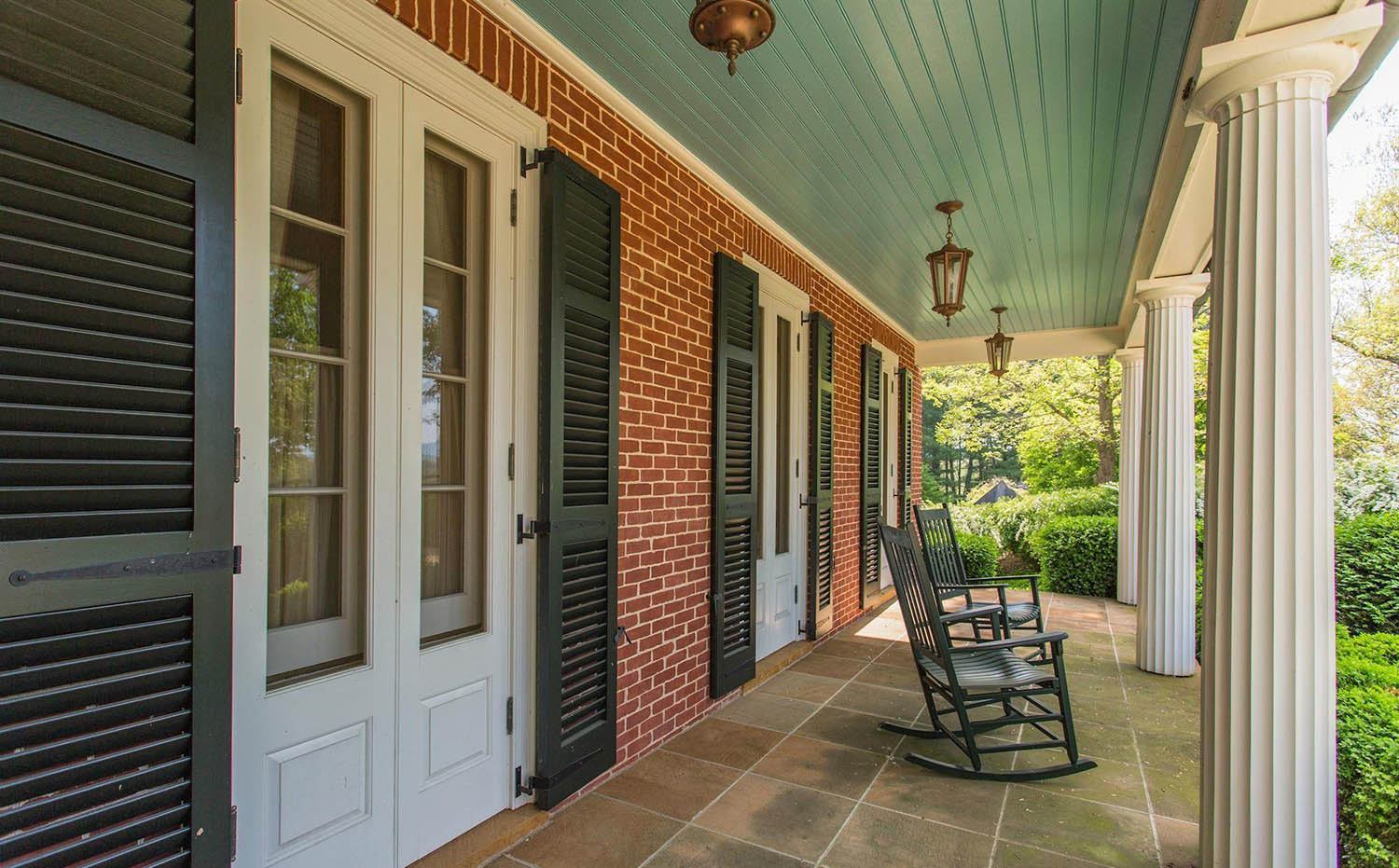 Front porch with white door and black shutters. Red brick.