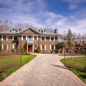 Red brick estate home with white trim and shutters. Real wood front door. Dormers. Gray roof chingles. Paver driveway.