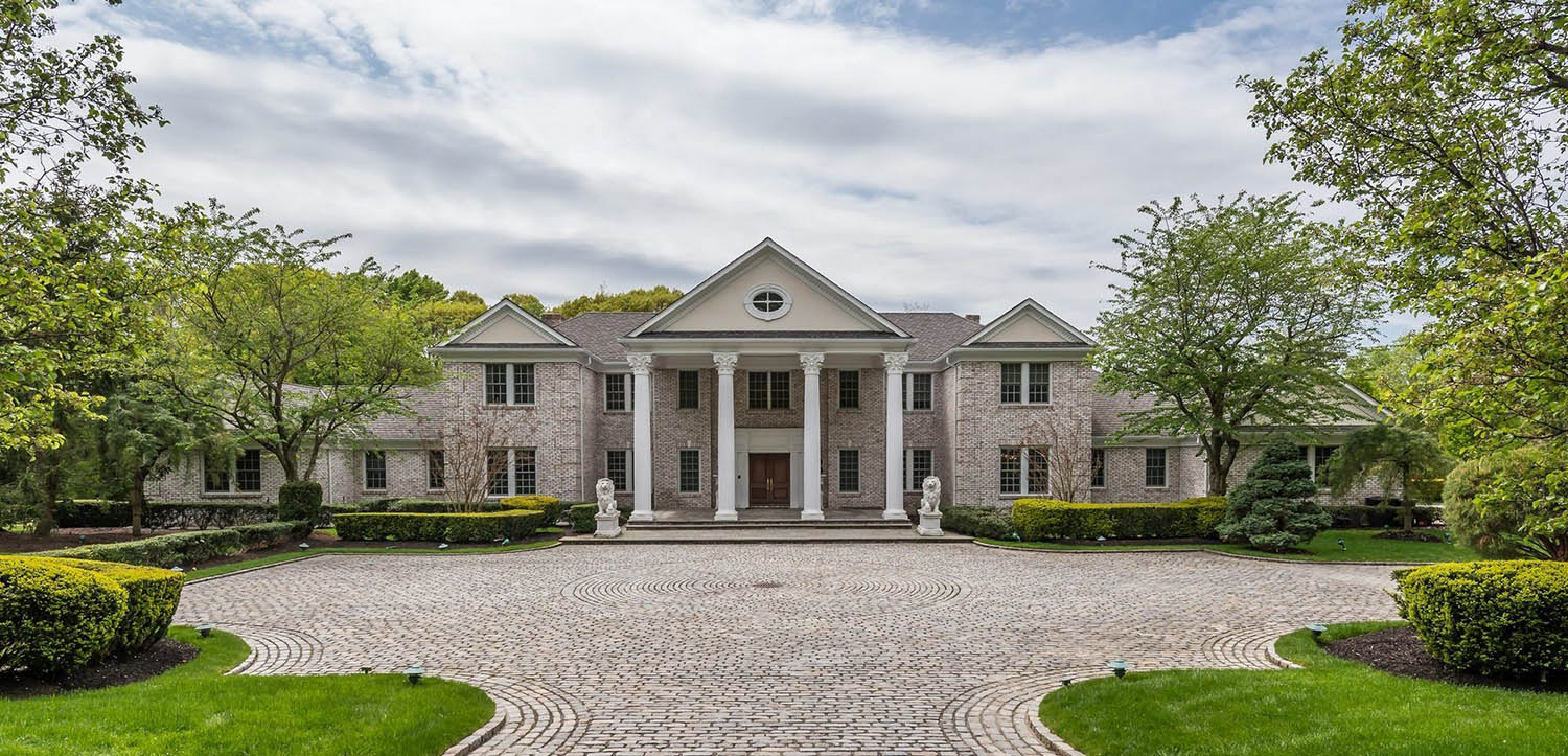 Large estate home with light colored brick and huge cement columns. Medium brown front door.
